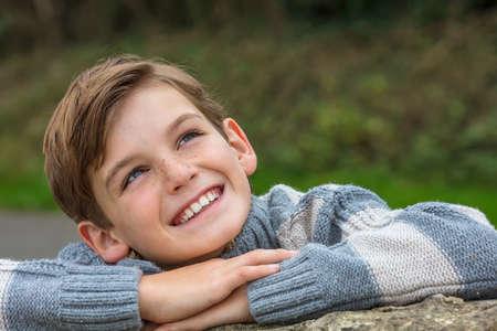 niños felices: risa feliz de sexo masculino de niño rubio joven fuera apoyándose en sus manos y mirando hacia arriba en el otoño de sol de otoño