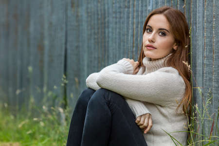 red hair girl: Outdoor portrait of beautiful thoughtful girl or young woman with red hair wearing a white jumper