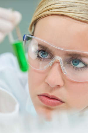 Female medical or research scientist or doctor using looking at a test tube of green solution in a lab or laboratory  photo