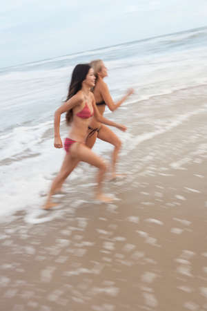 Motion blurred photograph of young women girls in bikinis running on a beach photo