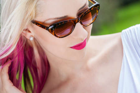 outdoor outside: Outdoor portrait of a beautiful young woman or girl with blond and pink hair wearing sunglasses outside