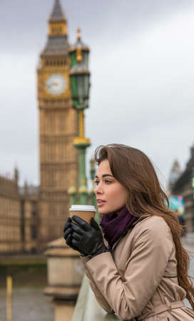 Girl or young woman drinking coffee in a disposable cup on Westminster Bridge with Big Ben in the background, London, England, Great Britain photo