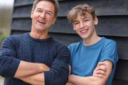 魅力的な成功と幸せの青いセーターと t シャツを着て、十代を笑うことの外彼の 10 代の少年息子と折り畳まれた中年の男の父男性腕ショット肖像画
