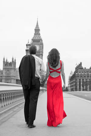 Black and white, rear view of romantic man and woman couple, the woman is wearing a red dress, on Westminster Bridge with Big Ben in the background, London, England, Great Britain