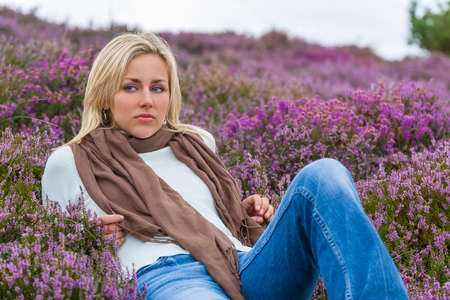 A naturally beautiful sad depressed young blond woman in a field of purple heather flowers photo
