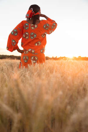 African woman in traditional clothes standing looking across field of barley or wheat crops at sunset or sunrise photo