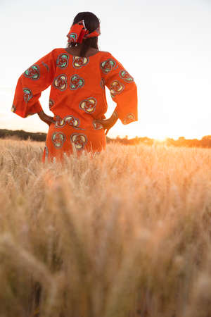 African woman in traditional clothes standing with her hands on her hips in field of barley or wheat crops at sunset or sunrise photo