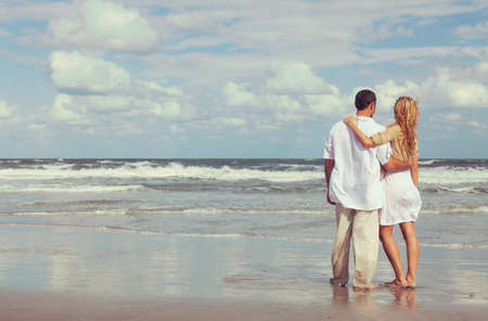 Instagram style photograph of romantic young man and woman couple embracing on a beach photo