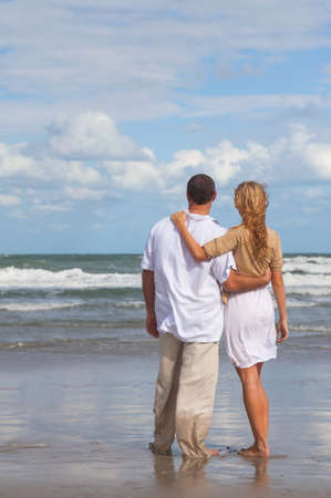Rear view of romantic young man and woman couple embracing on a beach photo