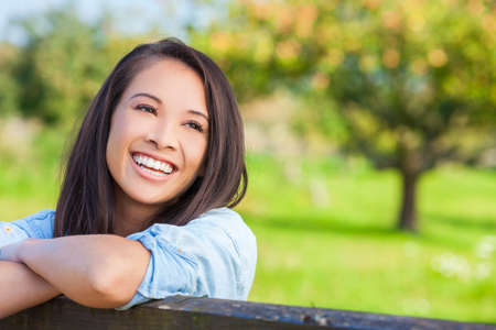 Beautiful happy Asian Eurasian young woman or girl wearing denim shirt, smiling with perfect teeth and leaning on fence in sunshine photo