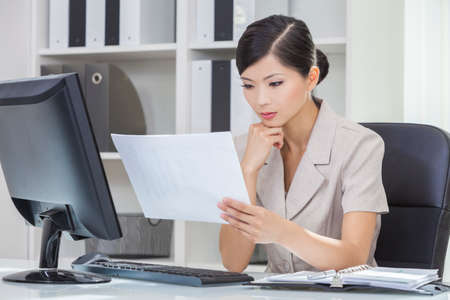 Portrait of a beautiful young Asian Chinese woman or businesswoman in office reading paperwork and using a computer photo
