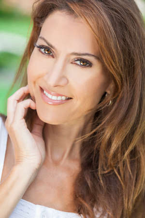 Outdoor portrait of a beautiful middle aged brunette woman in her forties photo