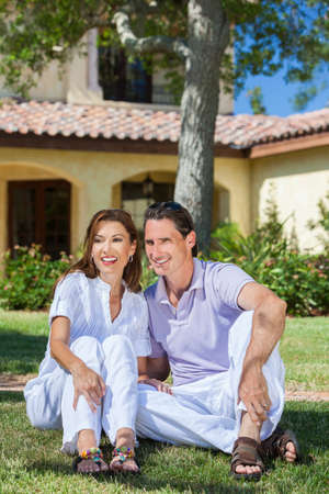 An attractive, successful and happy middle aged man and woman couple in their forties, sitting together outside under a tree and smiling. photo