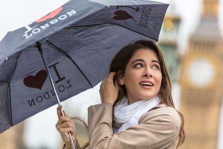 Girl or young woman tourist on vacation with an I Heart London umbrella with Big Ben in the background, London, England, Great Britain photo