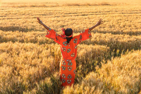 happy african: African woman in traditional clothes standing arms raised in a field of barley or wheat crops at sunset or sunrise Stock Photo