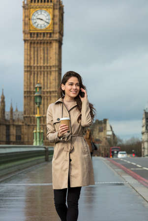 Girl or young woman walking across Westminster Bridge drinking coffee in a disposable cup and talking on a mobile cell phone with Big Ben in the background, London, England, Great Britain photo
