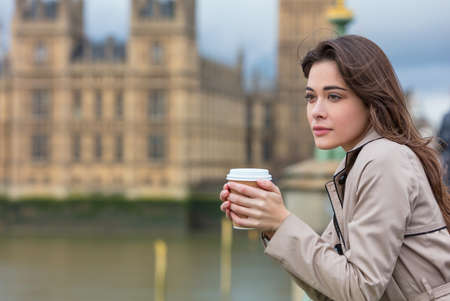 Beautiful sad, depressed or thoughtful young woman in London on Westminster Bridge over the River Thames drinking takeout coffee by Big Ben Stock Photo