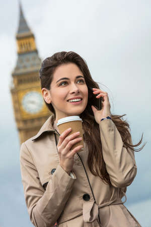 Girl or young woman with perfect teeth drinking coffee in a disposable cup and using a mobile cell phone with Big Ben in the background, London, England, Great Britain photo