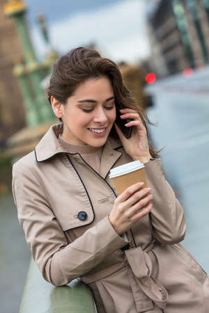 Happy, smiling, girl or young woman standing on Westminster Bridge, London, England, drinking coffee in a disposable cup and talking on a mobile cell phone photo