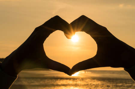 Hand heart frame shape silhouette made against the sun & sky of a sunrise or sunset on a deserted empty beach Stock Photo