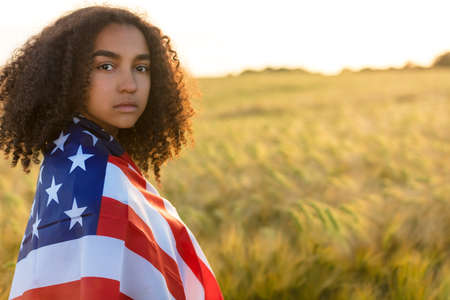 Young woman with tears in her eyes in a field of wheat or barley crops holding and wrapped in USA stars and stripes flag in golden sunset evening sunshine photo