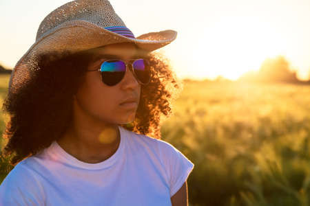 Beautiful happy mixed race African American female girl teenager young woman wearing relective aviator sunglasses and cowboy hat in a cornfield at golden sunset or sunrise photo