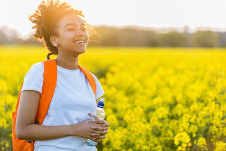 Outdoor portrait of beautiful happy laughing mixed race African American girl teenager female young woman with drinking water bottle in a field of yellow flowers at sunset in golden evening sunshine Stockfoto