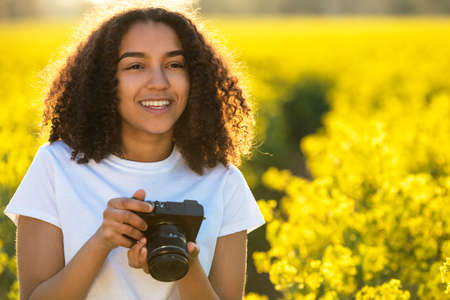 Beautiful happy mixed race African American girl teenager female young woman smiling outdoors in sunshine taking photographs with a camera photo