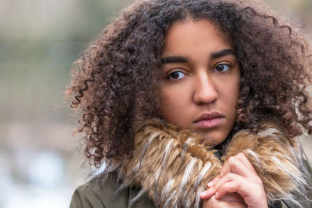 Beautiful mixed race African American girl teenager female young woman outside wearing fake fur collar coat looking sad depressed or thoughtful photo