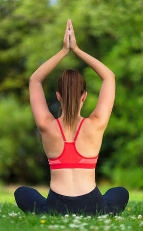 Rear view of young fit healthy woman female or girl practicing yoga pose on a mat outside in a natural tranquil green environment Stock Photo