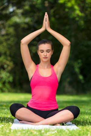 Young fit healthy woman female or girl practicing yoga pose on a mat outside in a natural tranquil green environment Stock Photo