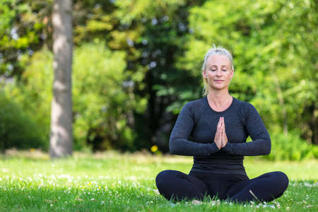 Mature middle aged fit healthy woman practicing yoga outside in a natural tranquil green environment