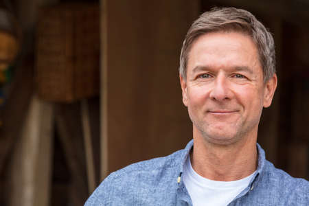 Portrait shot of an attractive, successful and happy middle aged man male wearing a blue shirt leaning on a post by a garage or barn Banco de Imagens