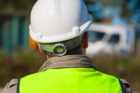 Rear view of construction worker on a building site and dressed in safety clothing of hard hat and high visibilty vest