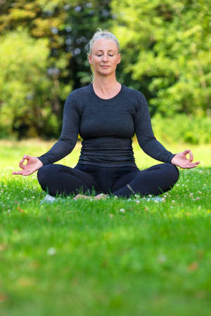 Mature middle aged fit healthy woman practicing yoga kapalbhati pranayama position outside in a natural tranquil green environment Stock Photo