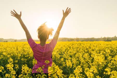 Gemengde ras African American meisje vrouwelijke jonge vrouw atleet runner tiener in gouden zonsondergang of zonsopgang opgeheven armen vieren in het veld van gele bloemen Stockfoto