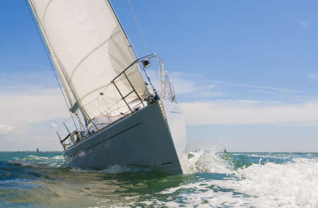 Close up of sailing boat, sail boat or yacht at sea on summer day with blue sky 写真素材