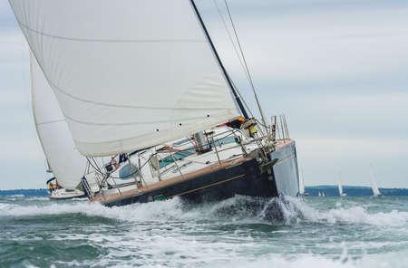 Two sailing boats, sail boats or yachts racing at sea