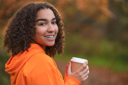 Beautiful happy mixed race African American girl teenager female young woman smiling with perfect white teeth,drinking coffee or tea outdoors in Fall or Autumn