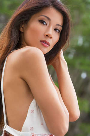 Outdoor portrait of a beautiful young Chinese Asian young woman or girl in summer sun dress Stock Photo