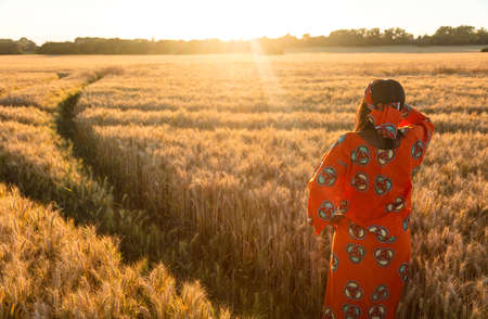 African woman in traditional clothes standing, looking to the sun, hand to eyes, in field of barley or wheat crops at sunset or sunrise