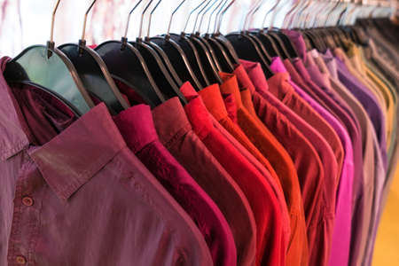 Male men's shirts sorted in color order on hangers on a shop wardrobe closet rail Stock Photo