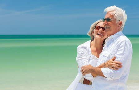 Glücklicher lachender älterer Mann und Frau zurückgezogenes Paar, das das Tragen der Sonnenbrille auf einem verlassenen tropischen Strand mit türkisfarbenem Meer und klarem blauem Himmel umarmt