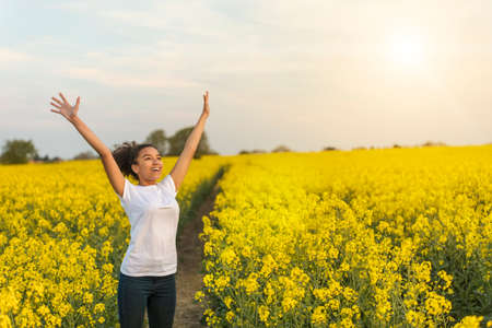 Outdoor portrait in golden evening sunshine of beautiful happy mixed race African American girl teenager female young woman smiling laughing arms raised celebrating in field of yellow flowers