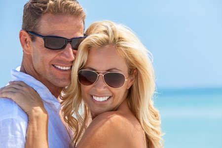 Glückliches und attraktives Mann- und Frauenpaar mit perfekten Zähnen, die Sonnenbrille tragen und im Sonnenschein am Strand lächeln