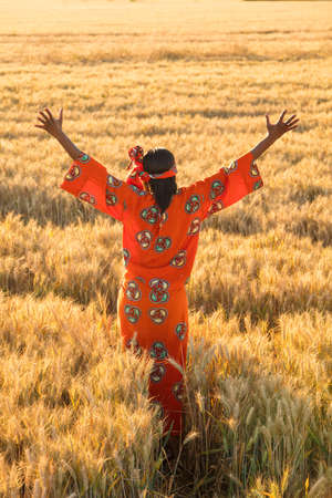 African woman in traditional clothes standing arms raised in field of barley or wheat crops at sunset or sunrise Imagens