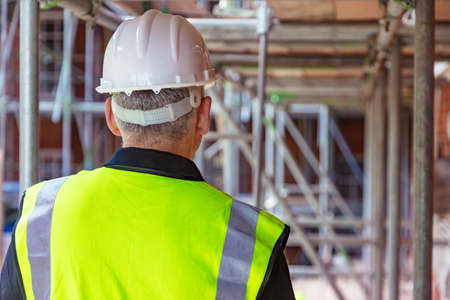 Widok z tyłu pracownika budowlanego konstruktora płci męskiej na budowie na sobie kask i kamizelkę odblaskową