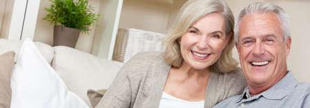 Imagen panorámica de banner web de feliz pareja senior hombre y mujer sentados juntos en casa sonriendo y felices con dientes perfectos