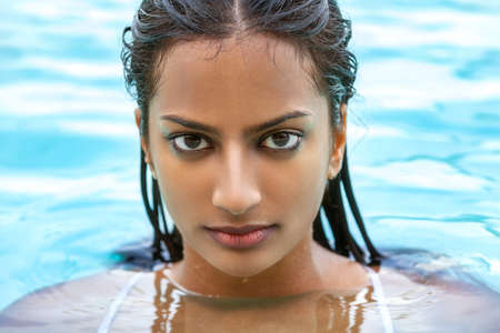 Portrait of beautiful sexy young Indian Asian woman or girl wearing bikini in swimming pool Banque d'images
