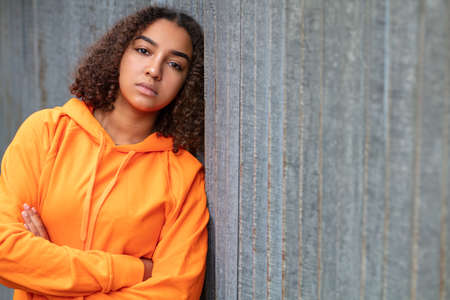 Beautiful mixed race African American girl teenager female young woman outside wearing an orange hoodie looking sad depressed or thoughtful Stok Fotoğraf